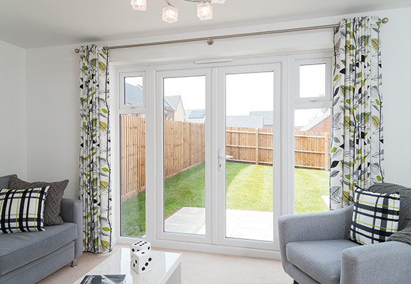 French glass doors in a white frame leading to backyard